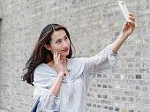 美しいアジアの女性は、スマートの mboile の電話を使用して selfie を撮影します。