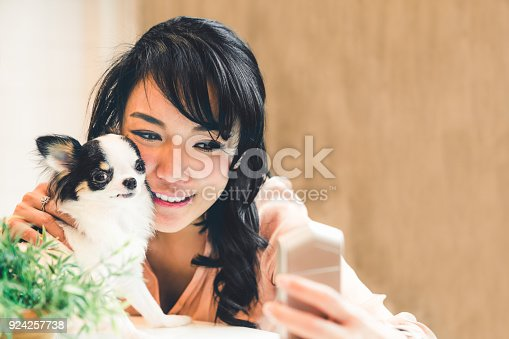 istock Beautiful Asian woman taking selfie with cute Chihuahua dog at home, with copy space. Lovely human and pet friendship, or modern domestic lifestyle concept 924257738