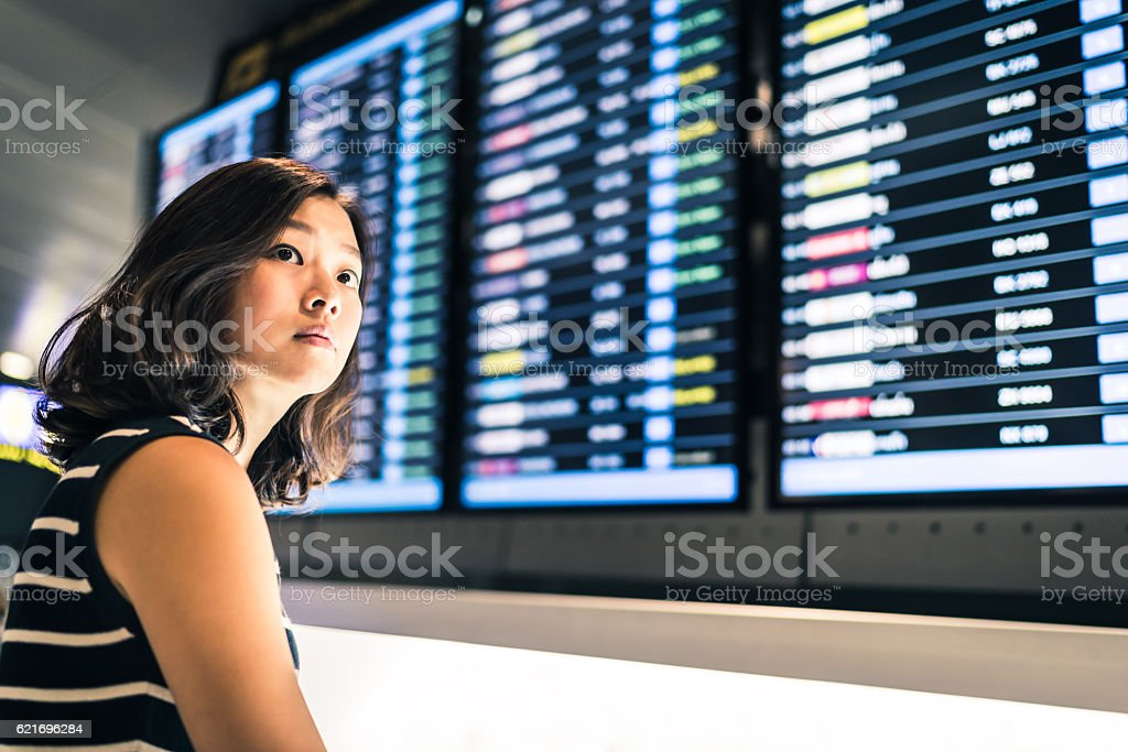 Beautiful Asian woman traveler at flight information screen stock photo