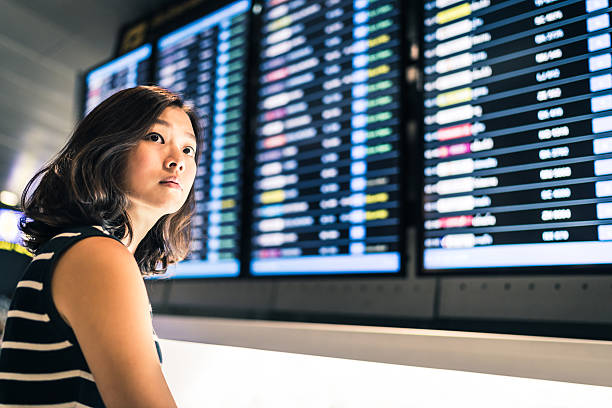Beautiful Asian woman traveler at flight information screen stock photo