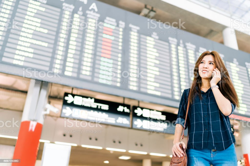 Beautiful Asian woman traveler on mobile phone call at flight information board in airport, holiday vacation travel or communication concept stock photo