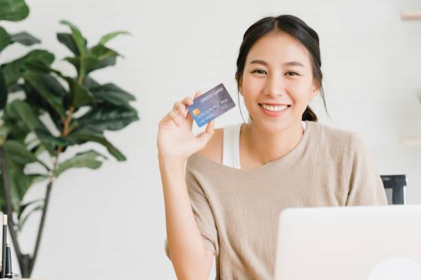 Schöne asiatische Frau mit Computer oder Laptop kaufen Online-Shopping mit Kreditkarte, während tragen Pullover sitzen auf Schreibtisch im Wohnzimmer zu Hause. Lifestyle Frau zu Hause Konzept. – Foto