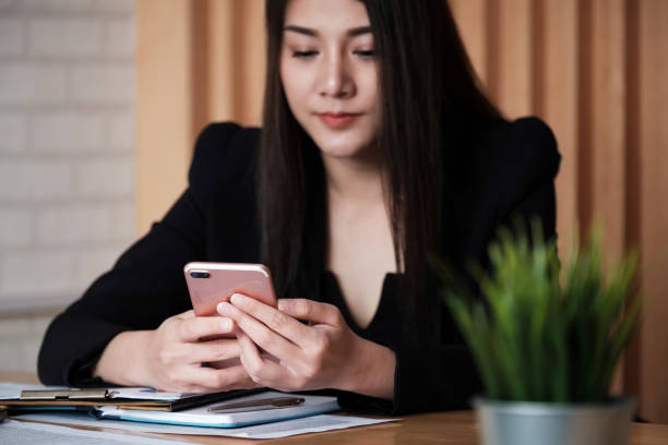 Eine schöne asiatische Frau mit auf dem Smartphone tippen Geschäftsnachricht. – Foto