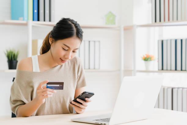 Schöne asiatische Frau, die Smartphone kauft Online-Shopping per Kreditkarte, während tragen Pullover sitzen auf Schreibtisch im Wohnzimmer zu Hause. Lifestyle Frau zu Hause Konzept. – Foto