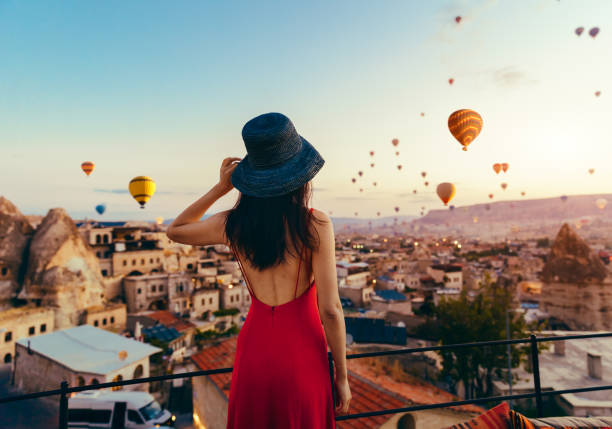 Beautiful asian woman watching  colorful hot air balloons flying over the valley at Cappadocia, Turkey. Turkey Cappadocia fairytale scenery of mountains. Woman, Hot Air Balloon, Sunset, Turkey - Middle East, Cappadocia, Air Vehicle turkish stock pictures, royalty-free photos & images