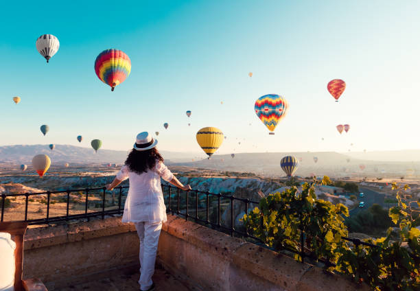 beautiful asian woman watching colorful hot air balloons flying over the valley at cappadocia, turkey.turkey cappadocia fairytale scenery of mountains. turkey cappadocia fairytale scenery of mountains. - travel imagens e fotografias de stock