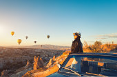 Beautiful asian woman watching colorful hot air balloons flying over the valley at Cappadocia,  Turkey Cappadocia fairytale scenery of mountains.