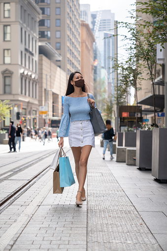 Beautiful Asian woman wearing a facemask on the street while shopping - pandemic lifestyle concepts