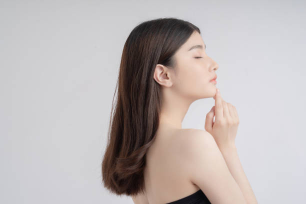 Beautiful asian woman with a beautiful face . Side view .She touches her chin stock photo