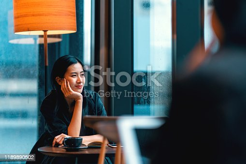 beautiful asian woman with long black hair looking out of window on a rainy day