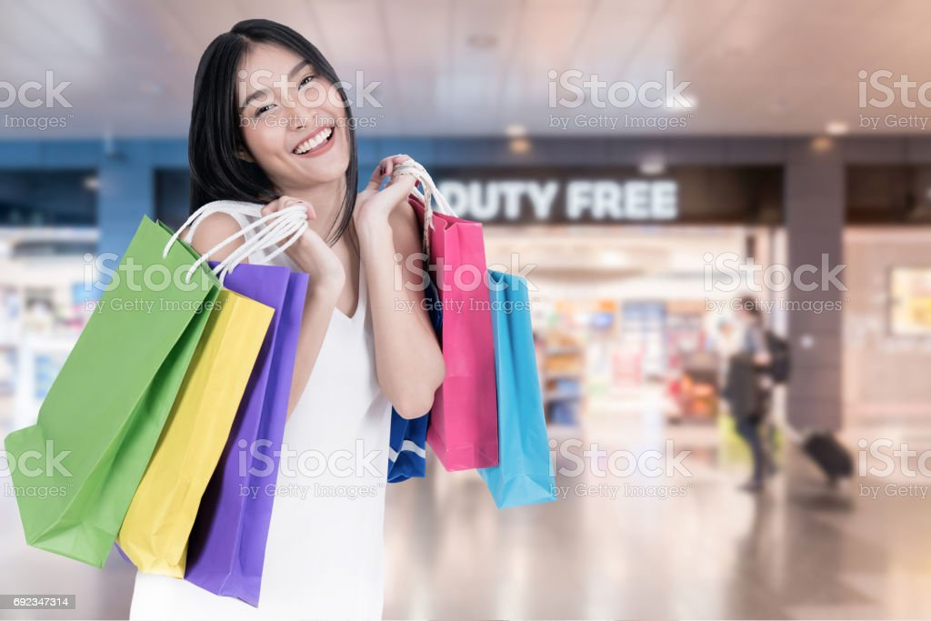 Beautiful Asian woman with shopping bags in duty free in International Airport before departure. Sale, shopping, tourism and happy people concept stock photo