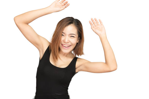 Beautiful asian women looking at camera with happiness smiling dancing put her hand up on white background stock photo