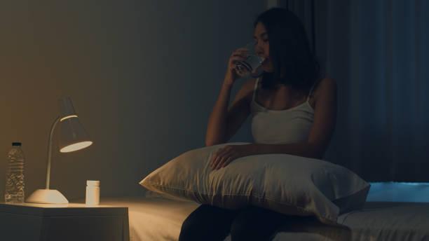 Schöne asiatische junge Frau sitzen auf dem Bett nehmen Schlaftablette oder Nacht Medizin im Schlafzimmer. Ungesunde kranke indische Frau leidet an Schlaflosigkeit oder Kopfschmerzen, depressive Mädchen hält Antidepressiva Medikamente. – Foto