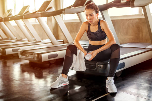 Beautiful Asian young woman tired taking a break from running or exercise sitting on treadmill machine drinking water and towel sweat in fitness gym healthy .girl in sportswear workout rest in morning stock photo
