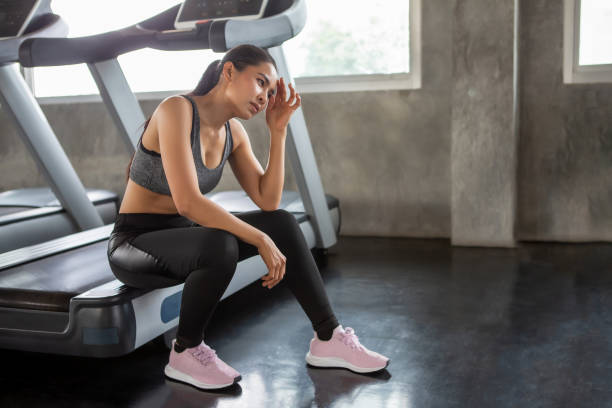 Beautiful Asian young woman tired taking a break from running or exercise sitting on treadmill machine  in fitness gym healthy .girl in sportswear workout rest in morning stock photo