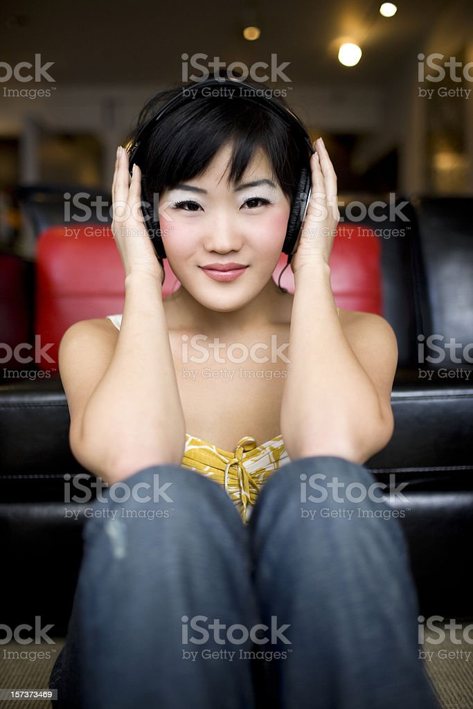 Beautiful Asian Young Woman Wearing Headphones in Modern Loft, Smiling royalty-free stock photo