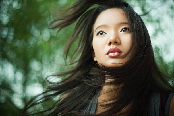 beautiful asian young woman with flying hair in nature. - beautiful curvy girls stock photos and pictures