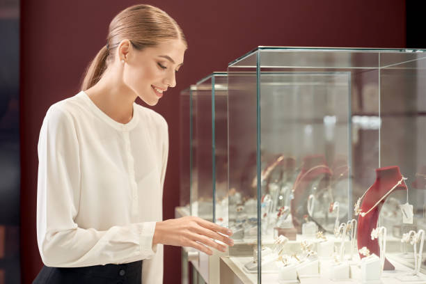 Beautiful assistant looking at showcase with luxury jewelry Beautiful lady with blond hair and tied knot in white silk blouse smiling and looking at showcase with luxury jewelry in store. Female assistant controling the appropriate look of precious metal. jeweller stock pictures, royalty-free photos & images