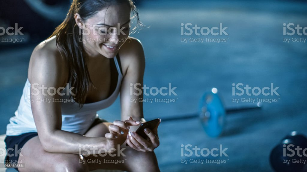 Güzel atletik esmer kullanır Smartphone Resting Her yoğun vücut geliştirme spor salonu eğitimden sonra bankta süre. - Royalty-free App Stok görsel