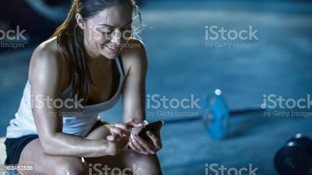 Schöne Sportliche Brünette Nutzt Smartphone Während Der Ruhepause Auf Der Bank Nach Ihrer Intensivtraining Der Bodybuildingfitnessstudio Stockfoto und mehr Bilder von Athlet