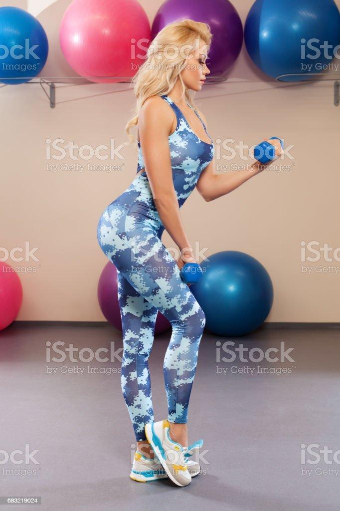 漂亮的運動女孩在健身室做運動。運動服運動婦女 免版稅 stock photo