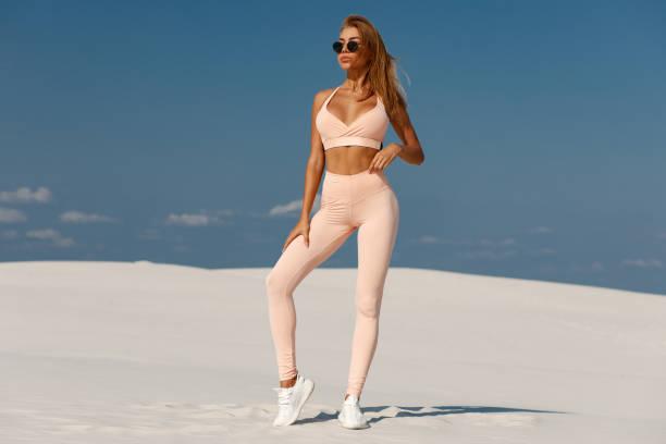 Beautiful athletic girl in sportswear, fitness woman in leggings outdoor stock photo