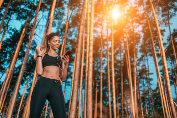schöne athletische mädchen hören musik mit kopfhörer joggen, hände smartphone glücklich lächelnd, sommerwald. freier weltraumtext. online-soziale netzwerke beobachten videos über internet kommuniziert in app. - wortarten bestimmen übungen stock-fotos und bilder