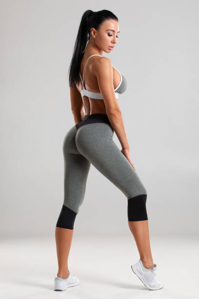 Beautiful athletic girl, sexy fitness woman in leggings on the gray background stock photo