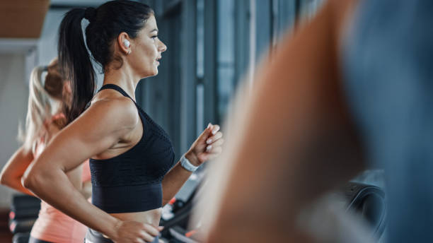 Beautiful Athletic Sports Woman Wearing Wireless Headphones, Listens to a Podcast or Sport Music Playlist while Running on a Treadmill. In Background Fit Athletes Training in the Gym Beautiful Athletic Sports Woman Wearing Wireless Headphones, Listens to a Podcast or Sport Music Playlist while Running on a Treadmill. In Background Fit Athletes Training in the Gym wireless headphones stock pictures, royalty-free photos & images