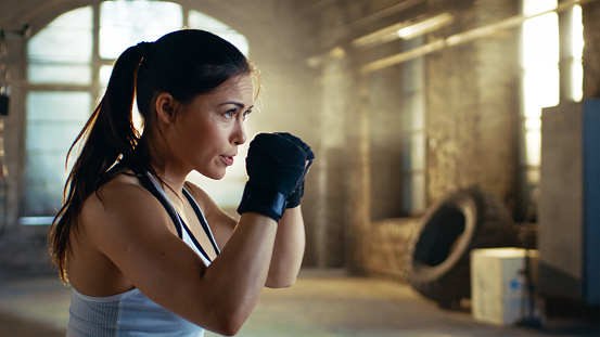 Beautiful Athletic Woman Holds Her Arms Ready For Defending Herself It Is A Part Of Her Intensive Cross Fitness Gym Training - Fotografie stock e altre immagini di Abbigliamento sportivo