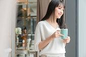 美しい魅力的なアジアの女性の新鮮さは幸せと自宅からラップトップコーヒーワークで働いて陽気な朝笑顔、庭の景色を楽しむ、窓の明るい庭の背景を持つアジアの若い女性