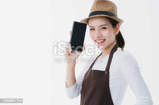 1066358064istockphoto beautiful attractive asian shop owner with apron present black screen smartphone with happiness and joyful business startup ideas concept 1056857724