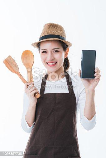 1066358064istockphoto beautiful attractive asian shop owner with apron present black screen smartphone with happiness and joyful business startup ideas concept 1056857736