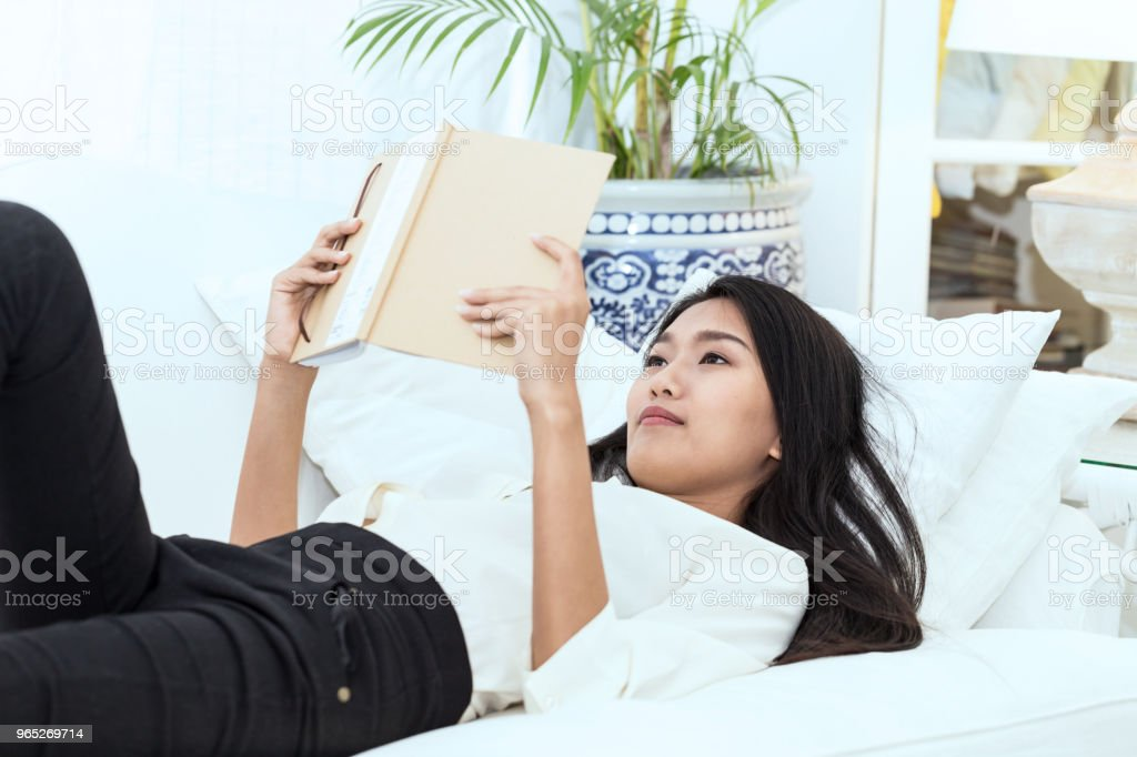 Beautiful Attractive Asian woman lying on sofa and relax with book in holiday feeling so relax and comfortable royalty-free stock photo
