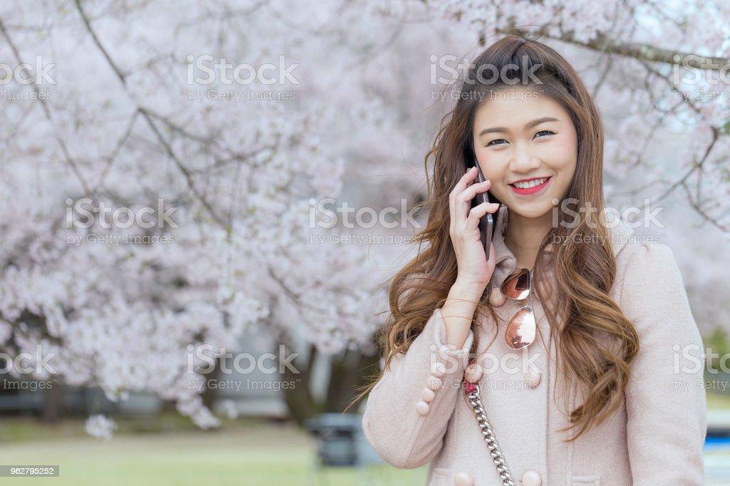 Linda mulher asiática atraente falando com o smartphone na Sakura ou flor de cerejeira fundo no Japão a sentir tanto orgulho e felicidade - Foto de stock de Adulto royalty-free