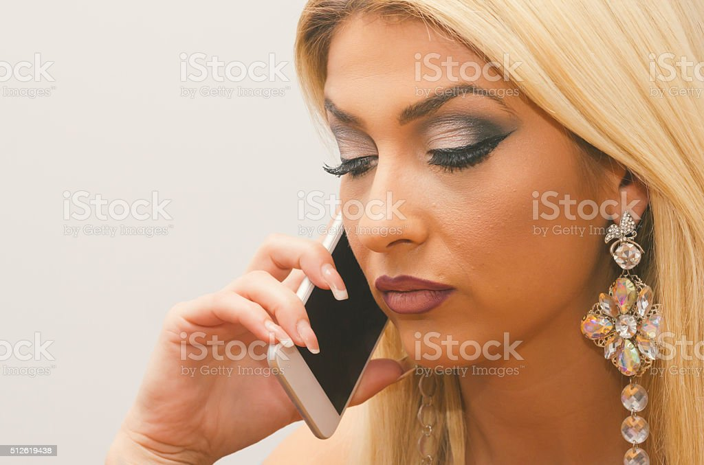 Beautiful, attractive blond girl talking to mobile phone stock photo