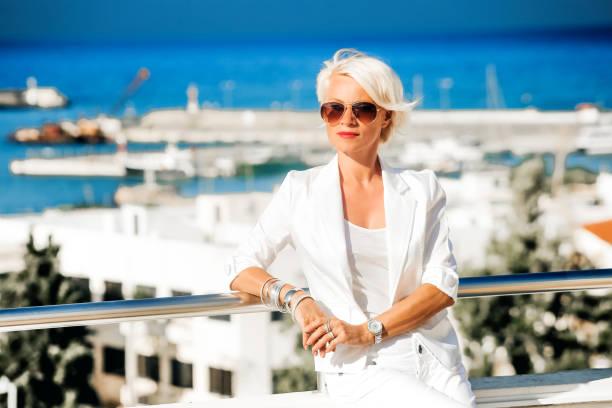 schöne, attraktive blonde geschäftsfrau im weißen anzug - damenschuhe 44 stock-fotos und bilder