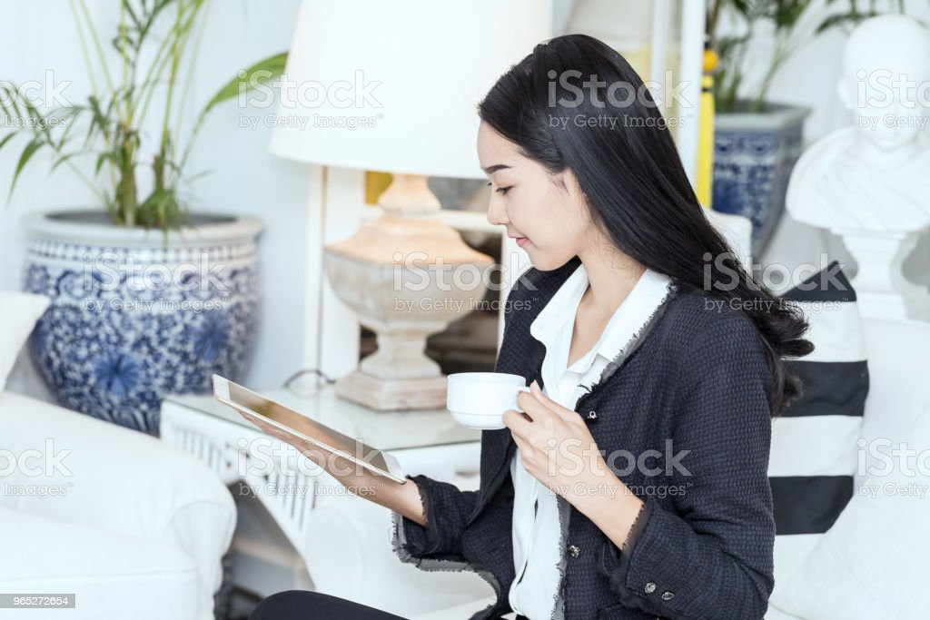 Beautiful Attractive Business Asian woman holding tablet and coffee in hand feeling so happiness and relax zbiór zdjęć royalty-free