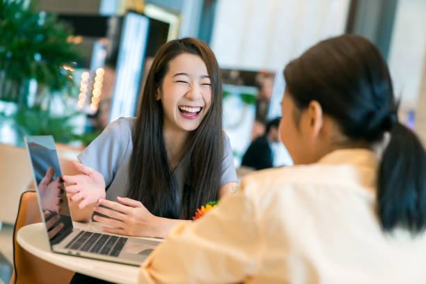 美しい魅力的なビジネス女性は、ラップトップと現代のオフィスの背景を持つクライアントに笑顔と喜びを持つ新しいプロジェクトを提示 - people of color ストックフォトと画像