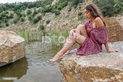 Beautiful  attractive caucasian  young woman sitting in dress on a stone in the lake