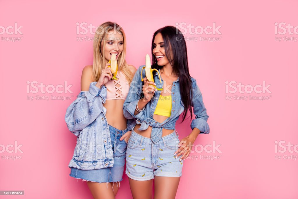 Beautiful attractive lovely careless charming flirty coquettish women clothed in denim stylish shirts, tops, shorts and skirt are fooling around and eating bananas, isolated on bright pink background stock photo