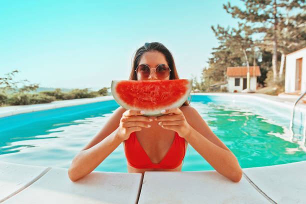 Beautiful, attractive woman enjoying in the pool, holding a watermelon stock photo