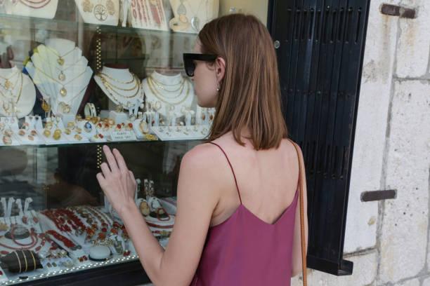 schöne attraktive junge frau in der nähe von schmuck schaufenster - diamanten kaufen stock-fotos und bilder