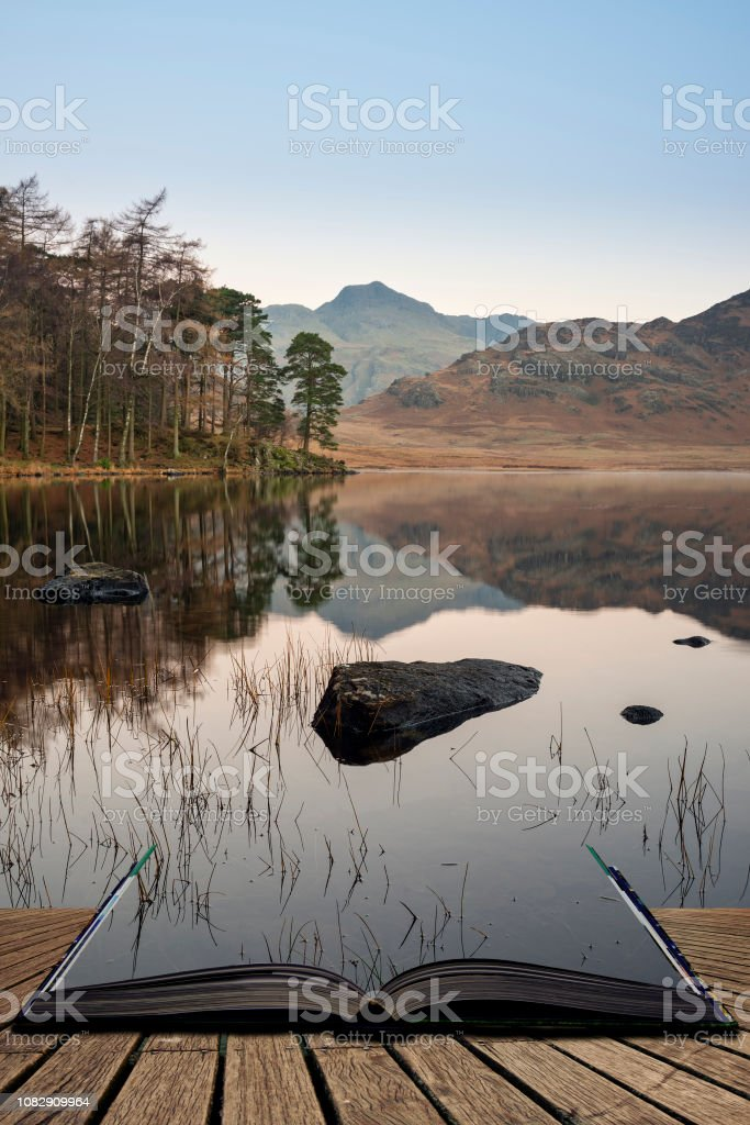 Beautiful Autumn Fall colorful sunrise over Blea Tarn in the Lake District with High Raise and The Langdales in the distance coming out of pages of open story book stock photo