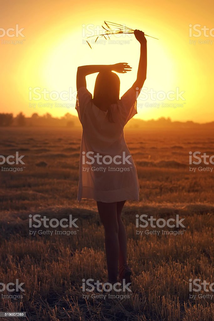 Beautiful autumn girl Girl goes the distance on an autumn meadow mown Holding Stock Photo