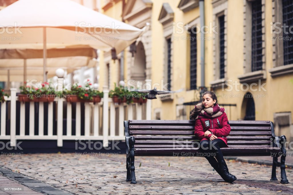 Beautiful autumn girl sitting on bench in middle of pavement on cafe background stock photo