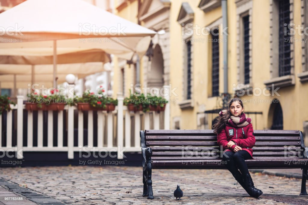 Beautiful autumn girl sitting on bench in middle of street on cafe background stock photo
