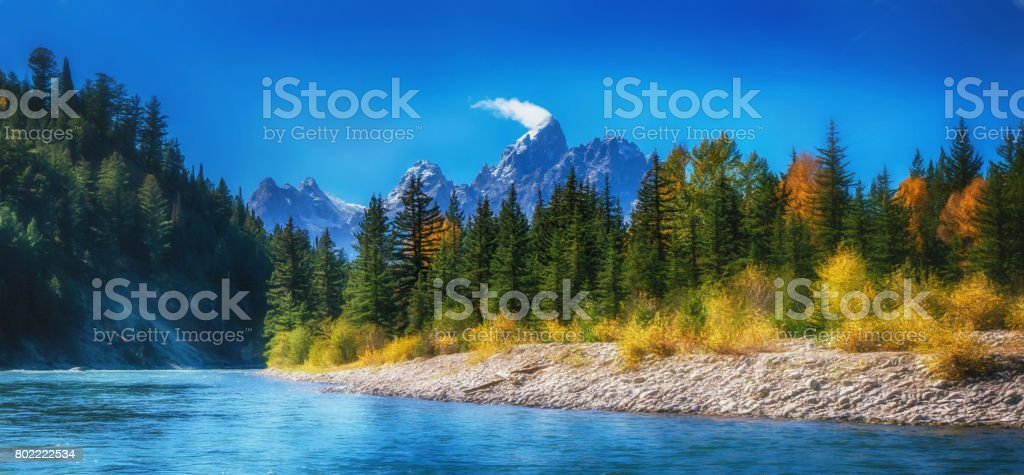 Beautiful autumn landscape scene in Grand Teton National Park, river flowing through evergreen forest with mountain range in the background. stock photo