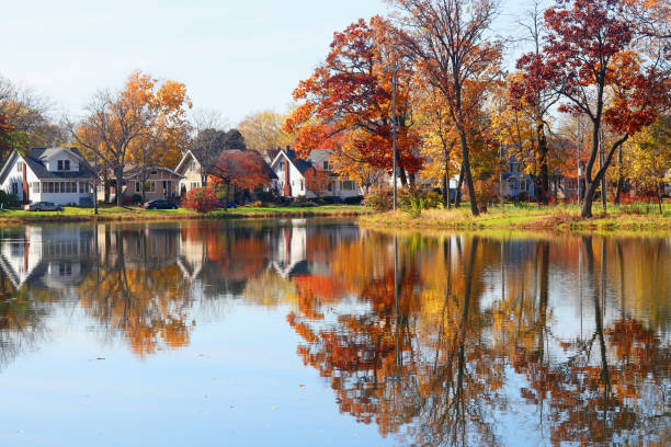 Beautiful autumn Midwest nature background. Fall view of private houses neighborhood with classic american middle class homes and colorful trees along a pond reflected in a water. Tenney Park, Madison, WI. madison wisconsin stock pictures, royalty-free photos & images