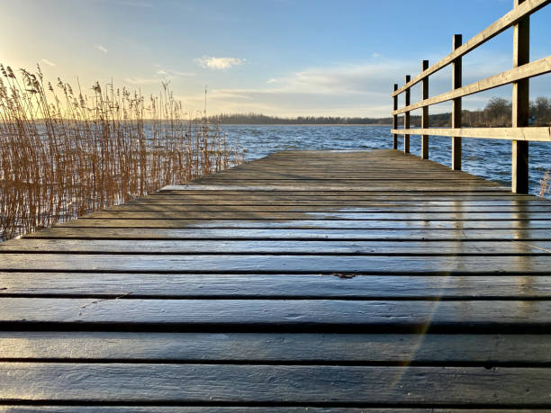 Beautiful autumn seascape sunset view with a wooden jetty, reed, horizon and sky. stock photo